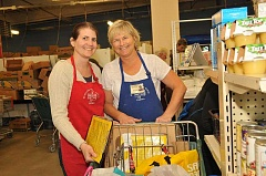 Photo Credit: STAFF PHOTO: VERN UYETAKE - Tualatin School House Pantry Program Coordinator Tracy Smith works with volunteer Joanne Clayton at the food pantry.
