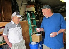 Photo Credit: BARBARA SHERMAN - LOOKING FOR ONE-OF-A-KIND BALLS - Larry McCullough (right) shows next-door neighbor Frank Heyl a few unusual golf balls he has discovered while cleaning thousands of them over the past few months.