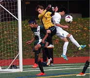 Photo Credit: DAN BROOD - IN THE AIR -- Tigard senior defender Sinan Raja (12) and junior goalie Pedro Simonetti battle Grant's Kyle Chin for the ball in Saturday's state playoff match.