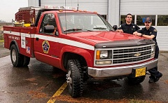 Photo Credit: RAY HUGHEY - Student firefighters Keith Nichols, left, and Austin Holmes with the Squad 65 truck.
