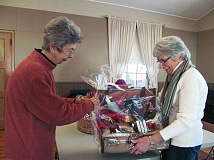 Photo Credit: CLACKAMAS REVIEW PHOTO: ELLEN SPITALERI - Audrey Trubshaw, left, and Nancy Doherty, chairman of the basket raffle, put the finishing touches on a basket to be raffled off during the 12th annual St. Nicholas Arts & Craft Faire, held Dec. 5 and 6 at St. Paul's Episcopal Church in Oregon City.