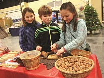 Photo Credit: TYLER FRANCKE - Salem residents and siblings, from left, Lillian, Henry and Rose Langen Swartzendruber take turns cracking hazelnuts with a wooden mallet at the Hazelnut Fest Saturday.