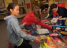 Photo Credit: REVIEW PHOTO: VERN UYETAKE - Chloe Carnegie (from left), Julia Siever and Bond Barnette sort through the toy donations.