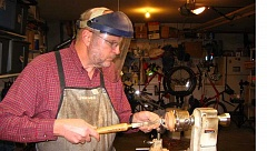 Photo Credit: GAZETTE PHOTO: RAY PITZ - Jim Burton turns a piece of wood to create a Christmas ornament on a lathe in his Sherwood garage. Wood to create the bowl came from a 120-year-old cedar taken down in Sherwood this past summer.