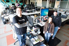 Photo Credit: KEVIN SPERL - Prineville residents, from left, Sam Viles, Karen Close, and Steve Duke work in an open-concept office area replete with monitoring stations, always keeping an eye on the computers that serve up Facebook's users 'walls.'