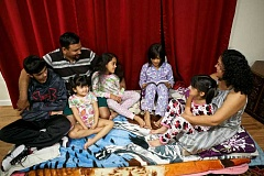 Photo Credit: TIMES PHOTO: JAIME VALDEZ - The Flores family listens to Mariana, age 9, read a chapter of The Lemoade War, as part of Durham Elementarys One School One Book program. From left, Christopher, 14, Pablo, Rosa, 4, Kassandra, 8, Mariana, Lillian, 6, and Nidia.