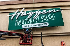 Photo Credit: SUBMITTED PHOTO - A Haggen employee hangs a sign at a newly converted store in Washington. Stores in Tigard and Sherwood will be converted in March, the company says.