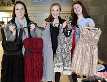 Photo Credit: REVIEW PHOTO: JILLIAN DALEY - National Charity League members (from left) Zoe Kiemel, Abby Castle and Ellie Howie hold up some of the  dresses students donated to Abbys Closet.