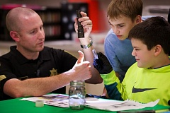 Photo Credit: OUTLOOK PHOTO: TROY WAYRYNEN - Sgt. Bryan White, left, with the Multnomah County Sheriffs office, shines light on his thumb during a CSI class at Clear Creek Middle School as students  Jake Cruz, 12, wearing yellow shirt, and Dyllan Torrey, 13, get a closer look.