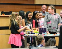 Photo Credit: HILLSBORO TRIBUNE PHOTO: DOUG BURKHARDT - Students from the Mooberry Elementary School girls engineering club demonstrate their Rube Goldberg device for members of the Hillsboro City Council. Left to right are Daisy Ixcolin-Pontaza, Mackenzie Kilpatrick and Jordan Thielke. Rube Goldberg was an American inventor and engineer whose whimsical devices used complicated chain reactions to perform simple tasks.