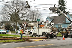 Photo Credit: DAVID F. ASHTON - A utility repair truck temporarily holds up telephone and cable lines, while a new utility pole is installed to replace the one snapped off at the base near 52nd and S.E. Ramona by a collision involving a minivan, on February 19.