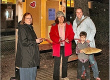 Photo Credit: DAVID F. ASHTON - Woodstock Librarian Carol Uhte, and Nicole Craigmiles with son Oliver, hold the ceremonial ribbon - as Woodstock Neighborhood Association Chair Becky Luening, with scissors, snips and dedicates the Woodstock Community Information Kiosk.