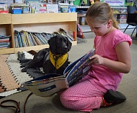 Photo Credit: SUBMITTED PHOTO: NICOLE PROM - Riverdale Grade School kindergartener Matilda Johnston reads to Lilah, a 3-year-old black Labrador.