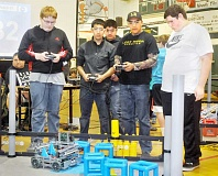 SETH GORDON - Dynamic duo - C.S. Lewis Academy sophomore Chad McLoughlin (left) controls he and junior Jacob Smits' (far right) robot during a preliminary match at the Oregon VEX State Championships. The duo advanced to the finals of the gold division.