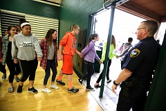 JONATHAN HOUSE - Twality Middle Schoolers hold hands as they leave the Tigard High gym en route to a designated spot where they would be reunited with their parents. The event was part of a disaster drill involving the Tigard-Tualatin School District and local law enforcement.
