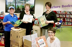 SUBMITTED - More books for kids - (From left) Kiwanis President Terry Molander and book drive chairwoman Joan Struchen join children's librarians Korie Buerkle and Mary Lynn Thomas in showing off the books the Kiwanis Club donated last week.