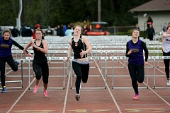 JOHN WILLIAM HOWARD - Scappoose junior Eleanor Jones, flanked by fellow Indian Mackenzie Ela and Astoria's Victoria Kee, reaches for the finish line in the final of the girls 100 meter hurdles at the Lower Columbia Invitational on Saturday, April 11.