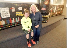 BARBARA SHERMAN - Deer Creek Elementary third-grader Dylan Portlock, sitting with his grandma Kathie Wilton outside the media center, has been lucky to have her volunteer every year since he started at the school.