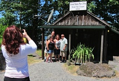 CONTRIBUTED PHOTO: QUINTON SMITH - Taking photos of soon-to-be brides, proud parents and tourists is part of the job for Bridal Veil Postmaster Tara Stiller. On Monday Stiller snapped a shot of Tina and Ron Calleros and James and Veronica Medina of Colton, Calif. who spotted the rustic post office on a trip to Multnomah Falls and stopped to mail postcards.