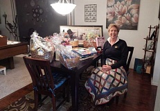 BARBARA SHERMAN - Sandy Brewer, chairwoman of the Summerfield Women's Golf Club's annual Charity Auction, sits with a few of the items that have been donated for the auction, which will be held in the Summerfield Clubhouse and is open to the public.