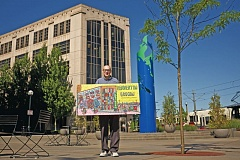 TIMES PHOTO: JAIME VALDEZ - Hillsboro Artist Justin Lacche stands in front of the Beaverton Building which gave him inspiration to paint, 'Afternoon at the Beaverton Building at The Round,' which he holds.
