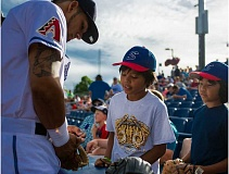 HILLSBORO TRIBUNE PHOTO: KENT FRASURE - Hillsboro Hops outfielder Gerard Hernandez signs a glove for a couple of young fans before the team's home opener on Tuesday night at Ron Tonkin Field.