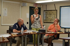 SPOTLIGHT PHOTO: MARK MILLER - Kathi Gobel, executive assistant to the St. Helens School District's board of directors and superintendent, holds up an hourglass that was the school board's parting gift for Mark Davalos, who was not at the meeting Wednesday, June 24. Also pictured: Gordon Jarman (left) and Jeff Howell (right), members of the school board.