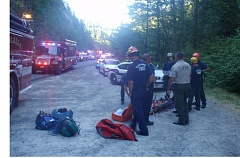 CLACKAMAS COUNTRY SHERIFF'S OFFICE - First responders stand near one of three men who were injured Thursday when their car went off a cliff along the Molalla Forest Road and rolled down a 40-foot drop before coming to rest along the edge of the Molalla River.
