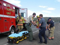 STEVE KADEL - First responders help Julie Alderman, 54, on Monday afternoon after the motorcycle she was riding with husband Alan Alderman crashed on Juniper Canyon Road.