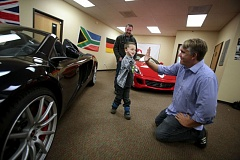 TRIBUNE PHOTO JONATHAN HOUSE - Shane gets a hi-five from Eric Peterson of Dream Drives for Kids as he and his grandfather Derek decide which car to take for a cruise.