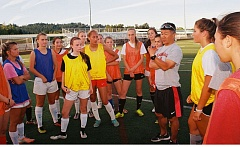 JOHN DENNY - Clackamas girls soccer coach Steve Lynch gets acquainted with some of his players during a break in a summer open play session at Clackamas High School.