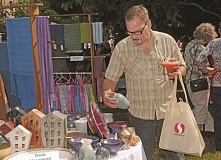CONNECTION PHOTO: VERN UYETAKE - John McReynold checks out the crafts sale at Multnomah Arts Center during last year's Multnomah Days. Vendors at the street fair will have a wealth of unique items for sale.