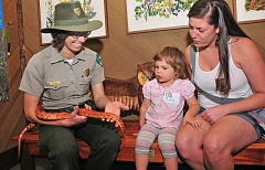 REVIEW PHOTO: VERN UYETAKE - Interpretive Park Ranger Deb Hill shows a corn snake to Ruby Anthony-Kain, 2, and Stephanie Lonsdale during Story and Stroll at Tryon Creek's Nature Center last Friday.