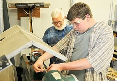 SETH GORDON - Sharing a passion - Chehalem Valley Sawdust Association president Tom Barnes assists his grandson, Clayton Barnes, as he uses a lathe at Chehalem Valley Middle School to create parts a wooden pen.