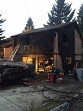 PHOTO COURTESY: CLACKAMAS FIRE - An attached garage and bedroom units on a house in Happy Valley are consumed by a fire on Thursday.