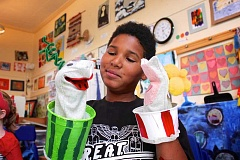 CONNECTION PHOTO: KELSEY O'HALLORAN - Kevyn Edwards, 11, shows off the healthy watermelon puppet and the unhealthy popcorn puppet that he made using recycled materials during the Southwest Youth Puppeteers Multnomah Days Parade Project at Multnomah Arts Center.