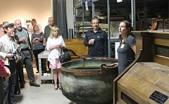 PAMPLIN MEDIA GROUP PHOTO: JOHN SCHRAG - Liza Schade, registrar for the Washington County Museum, shows a giant iron cauldron used to make Swiss cheese. Her audience includes Deanna Palm, chairwoman of Portland Community Colleges board of directors, and Hillsboro Mayor Jerry Willey (both behind the cauldron), among others.