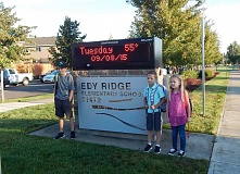 GAZETTE PHOTO: BARBARA SHERMAN - Edy Ridge fifth-grader Grady (left) and second-graders Abigail and Jaxon pose in front of the school's sign so their moms can take their photo before the first day of school Sept. 8.