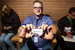 TIMES PHOTO: JAIME VALDEZ - Ron Beers, a Portland Community College custodian at the Rock Creek Campus, holds a card with a message that reads 'You are loved' that he hands out to students at campus.