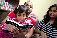 TRIBUNE PHOTO: JAIME VALDEZ - Pravisi Dandu with her parents at their Beaverton home. Shes already reading more books than they do.