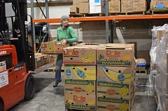 SPOTLIGHT PHOTO: NICOLE THILL - Columbia Pacific Food Bank employee Meredith Reading stacks boxes of canned goods in the warehouse. Boxes of fruits and vegetables were packed in the warehouse cooler for storage and will be delivered to Head Start locations next week.