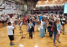 GAZETTE PHOTO: BARBARA SHERMAN - The Sherwood High School band formed two lines and played rousing music inside the large gymnasium Aug. 31 to welcome back the staff, who walked between the lines and found seats on the bleachers for the annual Back to School Rally.