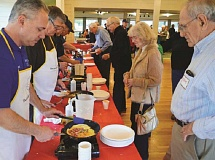 SPOKESMAN PHOTO: JAKE BARTMAN - Members of the Wilsonville Rotary Club prepared omelets for attendees at the clubs fourth annual breakfast in honor of veterans.