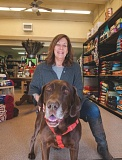 OUTLOOK PHOTO: JOSH KULLA - Kathi Krueger, owner of Second Nature Pet Food & Supplies in downtown Gresham, takes a break with her pet Labrador Brody in the storefront she relocated her business to earlier this fall.