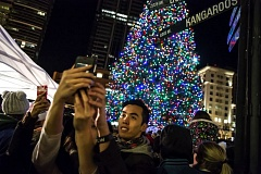 TRIBUNE PHOTO: JONATHAN HOUSE - Portland's Christmas Tree starred in dozens of selfies Friday afternoon during a lighting ceremony.