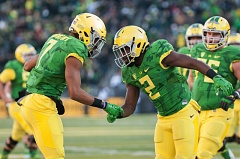 TRIBUNE PHOTO: JOSH KULLA - Bralon Addison (right) celebrates a touchdown with Darren Carrington, one of four Addison scored on the day for Oregon in the Ducks' 52-42 win at Autzen Stadium over Oregon State in the annual Civil War rivalry game.