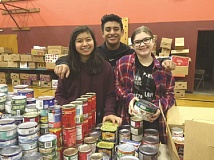 COURTESY PHOTO: ST. LUKE CATHOLIC SCHOOL - St. Luke eighth-graders (from left) Isabel Gonzalez, Mauricio Maravilla and Anna Koffler pack food boxes with St. Vincent de Paul for distribution to Woodburn families.