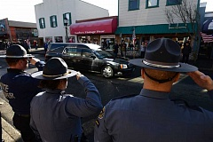JOSHUA BESSEX/THE DAILY ASTORIAN - Officers salute the hearse carrying Sgt. Jason Goodding as it arrives in downtown Seaside Friday
