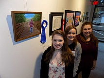 GAZETTE PHOTO: RAY PITZ - Kimbra Hern, Shyann Pfarr and Maria Landers, all seniors at Sherwood High School, pose in front of some of the artwork that is part of the Sherwood Center for the Arts first Student Art Show. It runs through April 4.