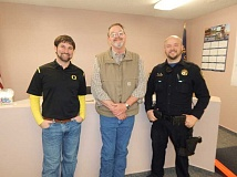 BARBARA SHERMAN - At the March 11 goodbye coffee for outgoing City Manager Dave Wells (center) at King City City Hall, he stands with new City Manager Michael Weston (left) and King City police officer Brian Sigler. Sigler has been chosen to teach the DARE (Drug Abuse Resistance Education) program at Deer Creek Elementary in King City next fall and will undergo training later this year.